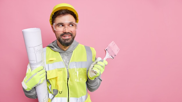 Trabalhador de reconstrução masculino profissional alegre sorri e desvia o olhar, vestido de uniforme, segurando um projeto arquitetônico e poses de pincel de pintura