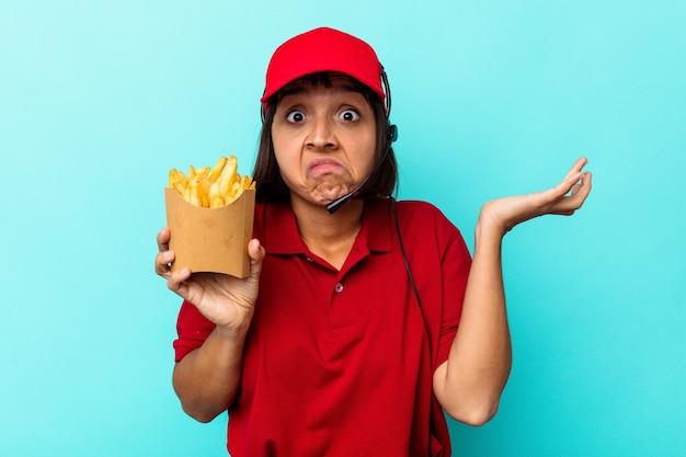 Trabalhador de restaurante de fast-food mulher jovem raça mista segurando batatas fritas isoladas no fundo azul encolhe os ombros e abre os olhos confusos.