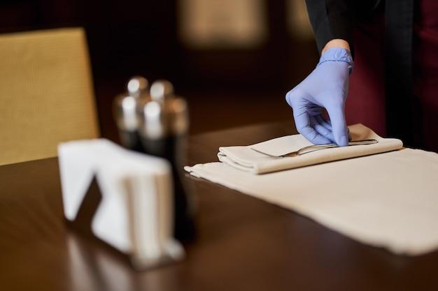 Trabalhador de restaurante usando luvas para arrumar mesas