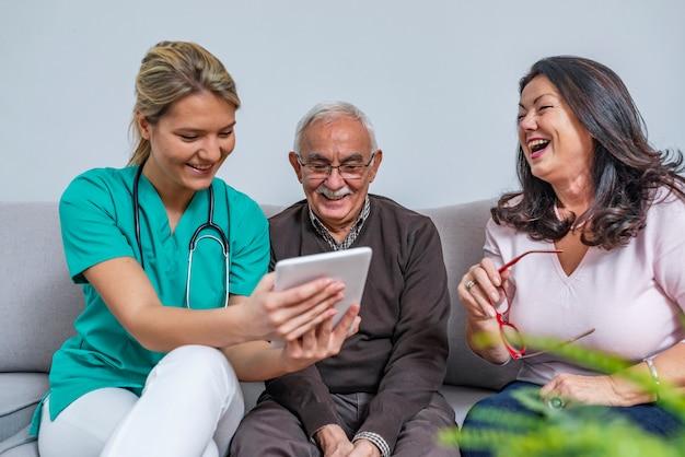 Trabalhador de saúde em casa e um casal de idosos