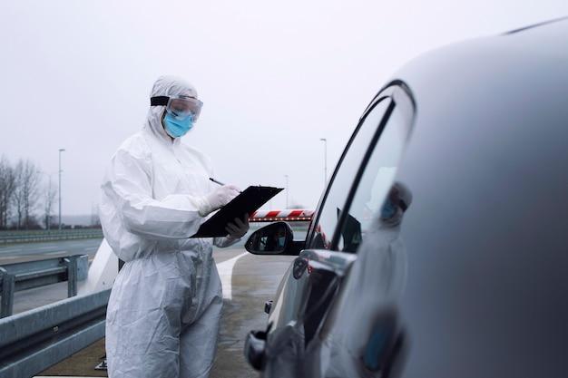 Trabalhador de saúde médica em traje protetor branco, controlando passageiros e teste de pcr na passagem de fronteira devido à pandemia do vírus corona global.