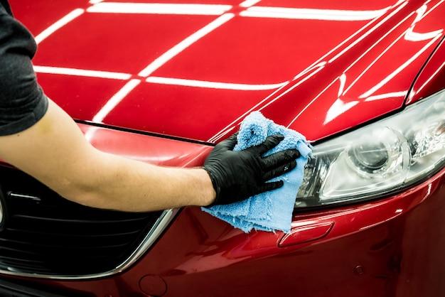 Trabalhador de serviço automóvel polindo o carro com pano de microfibra.