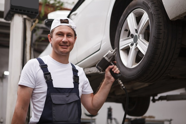 Trabalhador de serviço de carro alegre segurando a chave de torque elétrica, trabalhando na garagem