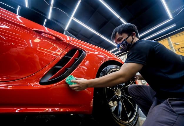 Trabalhador de serviço de carro aplicando revestimento nano em um detalhe do carro