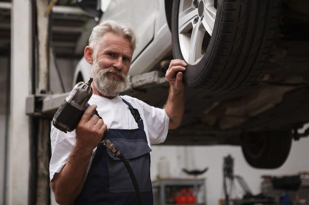 Trabalhador de serviço de carro barbudo idoso segurando a chave dinamométrica, em pé perto do carro levantado, copie o espaço