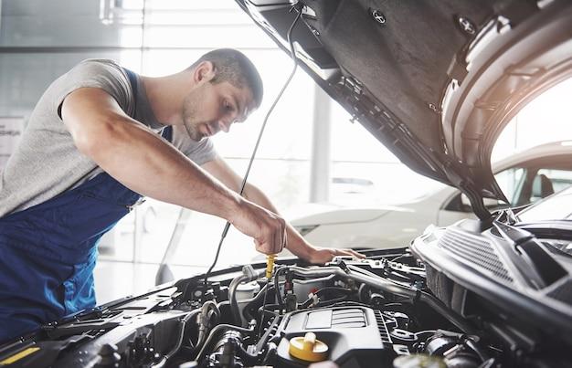 Trabalhador de serviço de carro muscular, reparando o veículo.