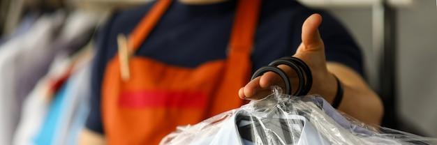 Trabalhador de serviço de limpeza a seco de roupas, devolvendo camisas ao cliente