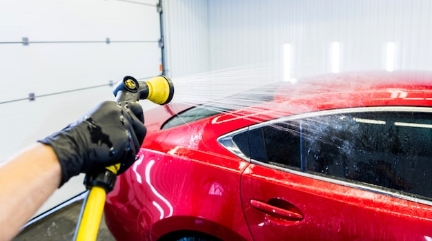 Trabalhador de serviço lavando carro em um lava-rápido.