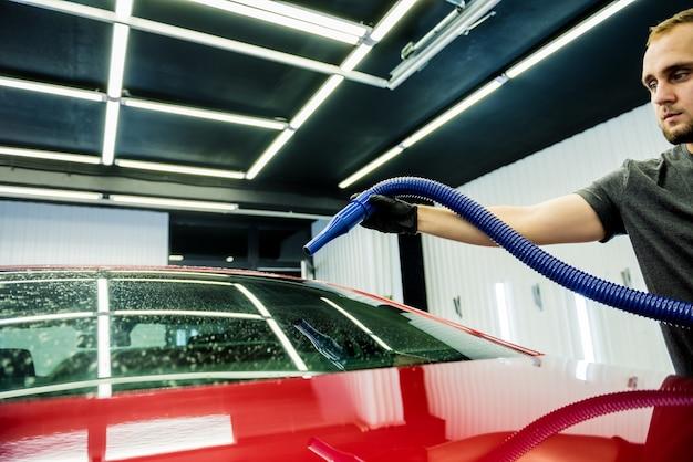 Trabalhador de serviço secando um carro