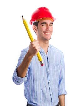 Trabalhador de sorriso com capacete de segurança e lápis