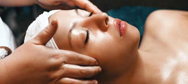 Trabalhador de spa caucasiano terminando uma sessão de massagem facial no spa com uma linda mulher