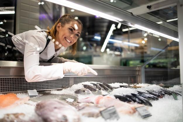 Trabalhador de supermercado organizando peixe congelado para venda