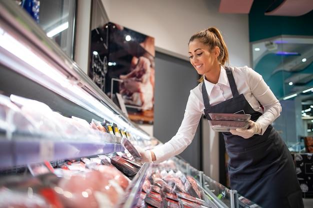 Trabalhador de supermercado organizando posição no departamento de carnes