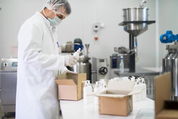 Trabalhador de tecidos cosméticos tomando um sabonete líquido de uma linha e colocando em uma caixa de papel para transporte