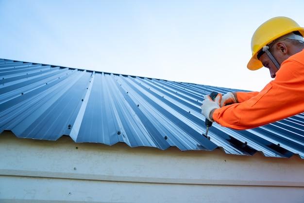 Trabalhador de telhados com uniforme de proteção e instalação de telhado novo