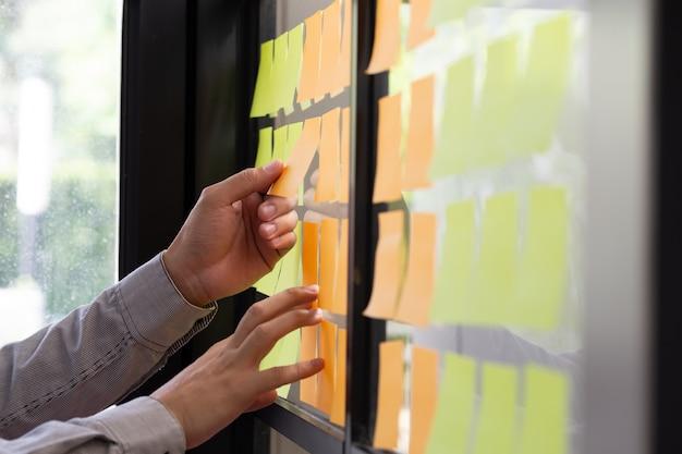 Trabalhador de ti, rastreando suas tarefas no quadro kanban.