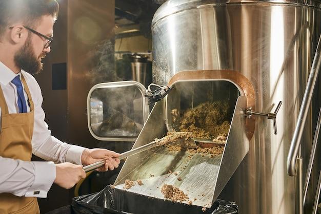 Trabalhador de uma cervejaria adulto, bonito, de óculos, camisa branca e avental marrom segurando uma pá com grãos de malte moídos. conceito de fabricação de cerveja. processo de fragmentação do malte.