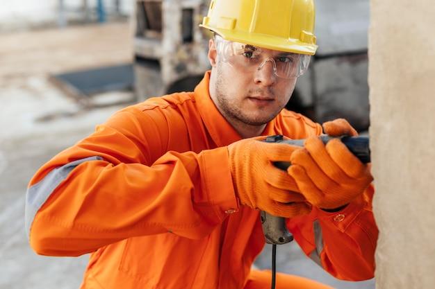 Trabalhador de uniforme com óculos de proteção e broca