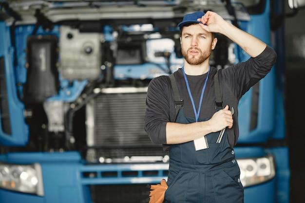 Trabalhador de uniforme. homem conserta um caminhão. homem com ferramentas