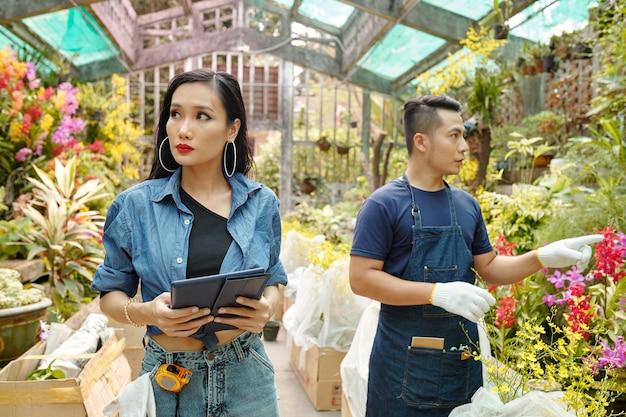 Trabalhador de viveiro de flores ajudando paisagista a escolher plantas para seu projeto