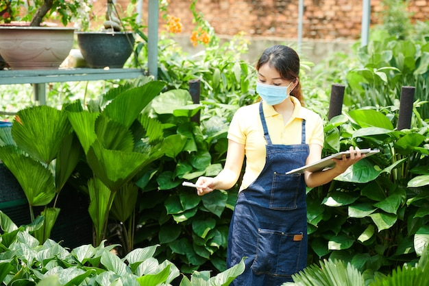 Trabalhador de viveiro de plantas com máscara protetora, verificando a lista de plantas que ela precisa enviar aos clientes