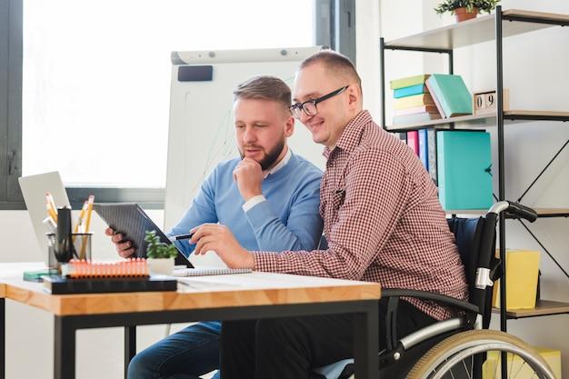 Trabalhador deficiente positivo junto com o gerente no escritório