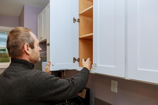 Trabalhador define uma nova alça no gabinete branco com uma chave de fenda instalando armários de cozinha