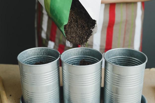 Trabalhador derrama solo no vaso de flores