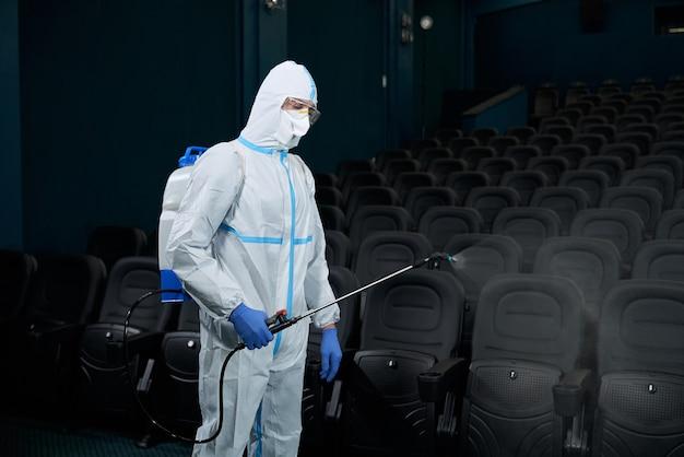 Trabalhador desinfeta a sala de cinema contra o coronavírus.