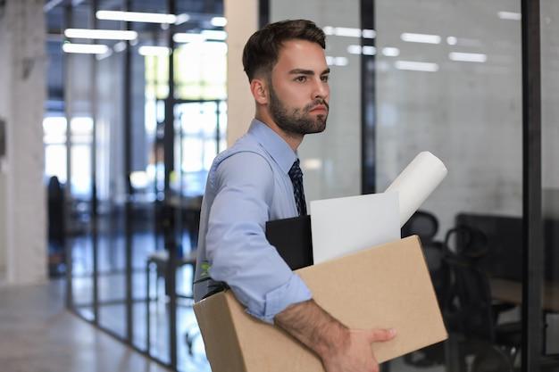 Trabalhador despedido triste está levando seu material de escritório com ele do escritório.