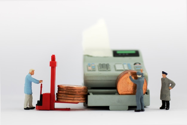 Trabalhador diminuto com pilha da moeda.