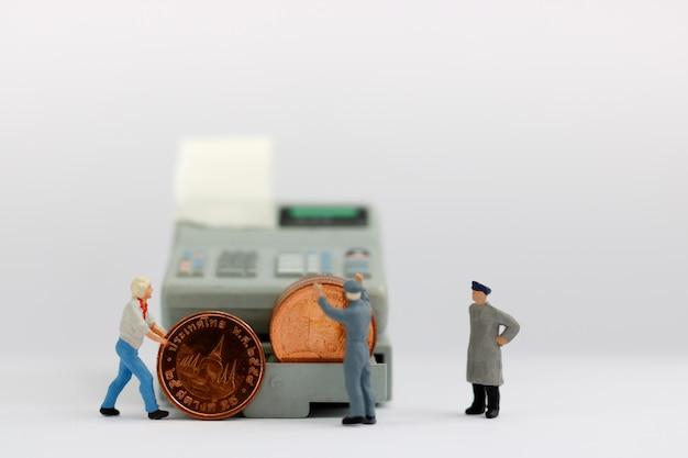 Trabalhador diminuto com pilha de moedas.