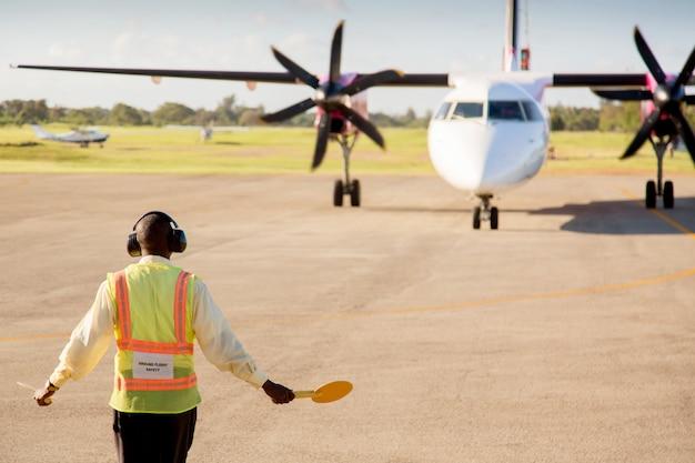 Trabalhador do aeroporto sinalizando e dirigindo um avião na pista do aeroporto