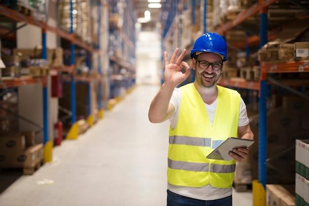 Trabalhador do armazém em pé no grande centro de armazenamento e mostrando um gesto de ok com a mão satisfeito ao entregar as mercadorias