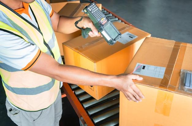 Trabalhador do armazém está digitalizando scanner de código de barras com caixas de embalagem.