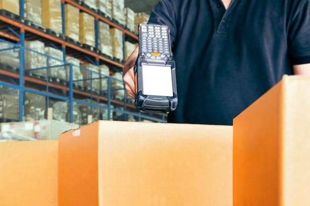 Trabalhador do armazém está digitalizando scanner de código de barras com caixas de papelão.