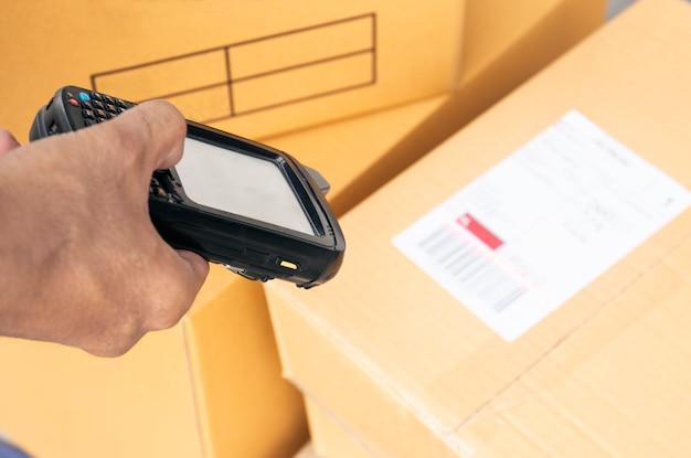 Trabalhador do armazém está digitalizando scanner de código de barras com etiqueta do produto.