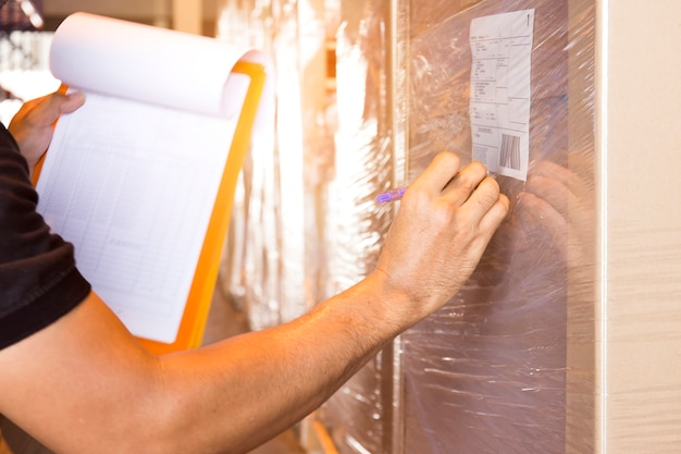 Trabalhador do armazém estão segurando uma prancheta com o inventário do produto.