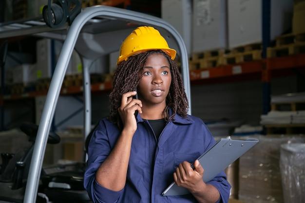 Trabalhador do armazém preto focado no capacete de segurança amarelo em pé perto da empilhadeira e falando no celular. prateleiras com mercadorias em segundo plano. tiro médio. trabalho ou conceito de comunicação