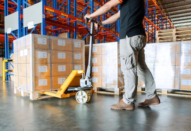Trabalhador do armazém que trabalha com o caminhão de pálete da mão e a carga no armazém.
