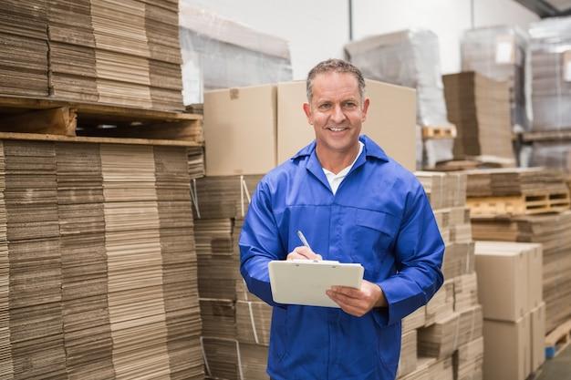 Trabalhador do armazém verificando sua lista na área de transferência