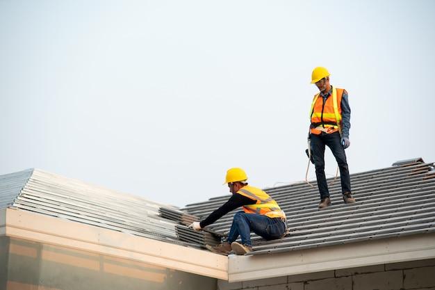Trabalhador do carpinteiro no desgaste uniforme protetor e luvas, usando a pistola de pregos pneumática ou pneumática e instalando a telha de telhado de concreto sobre o telhado novo, conceito de edifício residencial em construção.