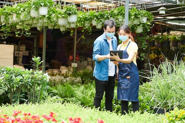 Trabalhador do centro de jardinagem mostrando fotos de flores em um tablet para o cliente e ajudando-o a fazer o pedido