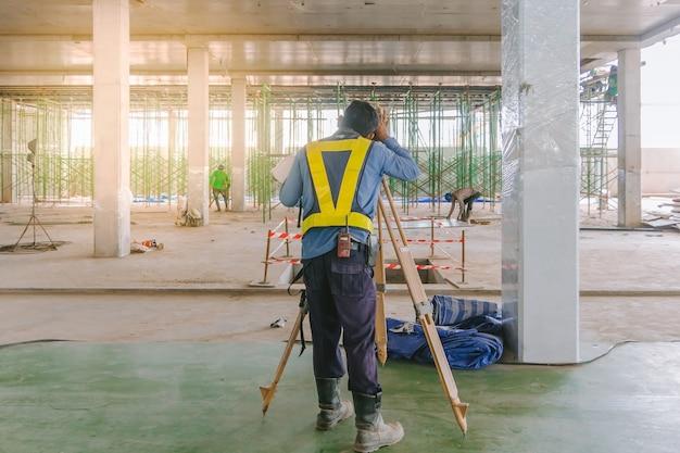 Trabalhador do coordenador do topógrafo que faz a medição com equipamento do teodolito no canteiro de obras.