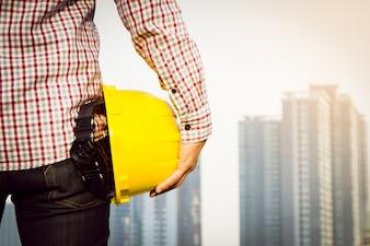 Trabalhador do engenheiro da mão que segura o capacete de segurança amarelo com a construção no fundo do local.