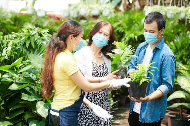 Trabalhador do mercado de plantas explicando aos clientes como cuidar das plantas que estão comprando para casa e jardim
