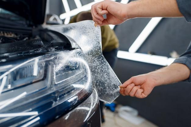 Trabalhador do sexo masculino aplica filme de proteção do carro no pára-lama dianteiro. instalação de revestimento que protege a pintura do automóvel de arranhões. novo veículo na garagem, procedimento de ajuste