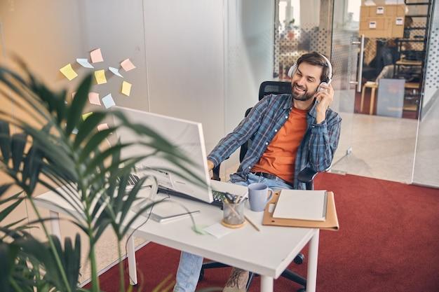 Trabalhador do sexo masculino bonito usando fones de ouvido, assistindo a um vídeo no pc de mesa e sorrindo enquanto está sentado à mesa no escritório