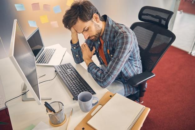 Trabalhador do sexo masculino cansado olhando para baixo e apoiando a cabeça com a mão enquanto está sentado à mesa com o computador e laptop