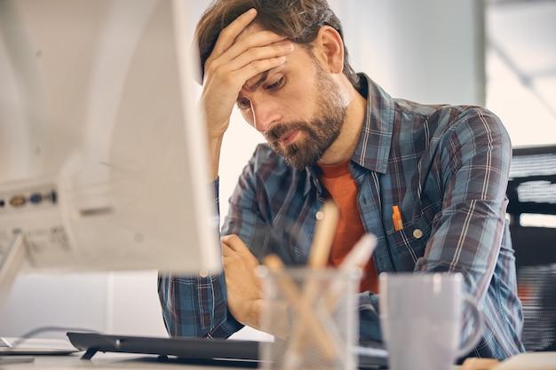 Trabalhador do sexo masculino cansado olhando para baixo e tocando a testa enquanto está sentado à mesa com o pc de mesa no escritório